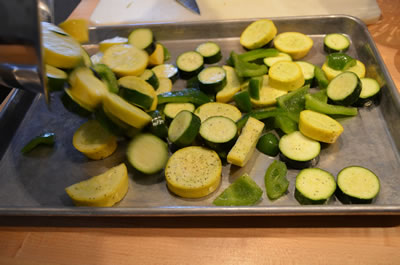 On separate unlined sheet tray spread out squash and pepper mixture.